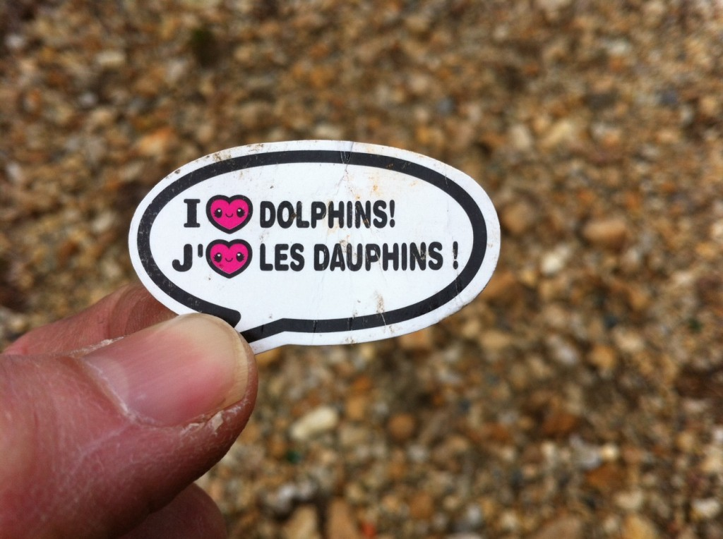 """A tiny sticker that says """"I (heart) dolphins, J' (heart) les daupins"""""""